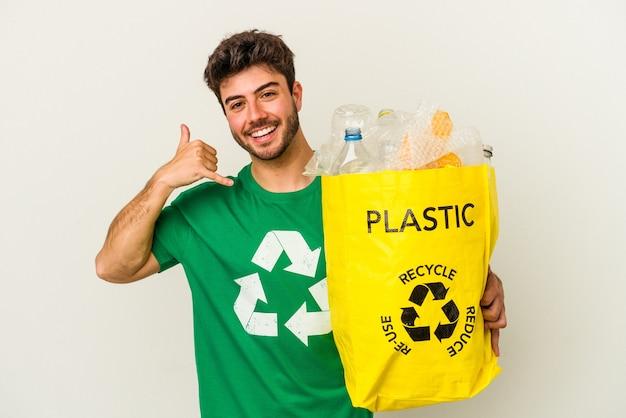 Jovem homem caucasiano, reciclando plástico isolado no fundo branco, mostrando um gesto de chamada de telefone móvel com os dedos.