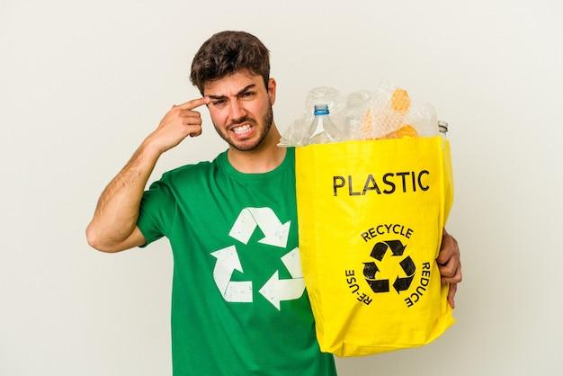 Jovem homem caucasiano, reciclando plástico isolado no fundo branco, mostrando um gesto de decepção com o dedo indicador.