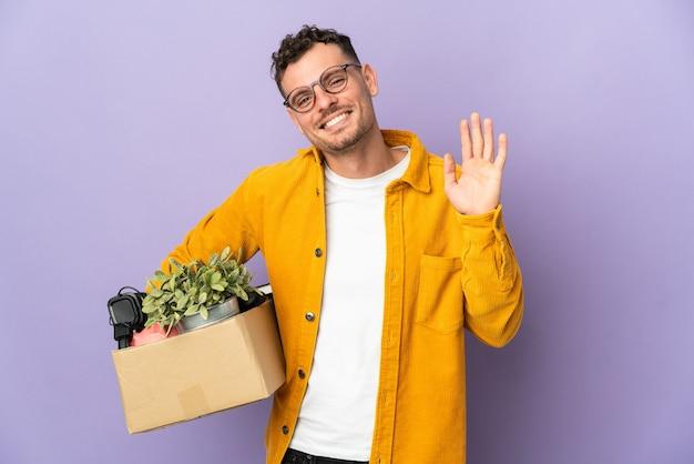 Jovem homem caucasiano se mexendo enquanto pega uma caixa cheia de coisas isoladas