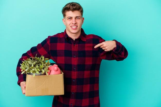 Jovem homem caucasiano se movendo segurando uma caixa isolada em um fundo azul pessoa apontando com a mão para um espaço de cópia de camisa, orgulhoso e confiante