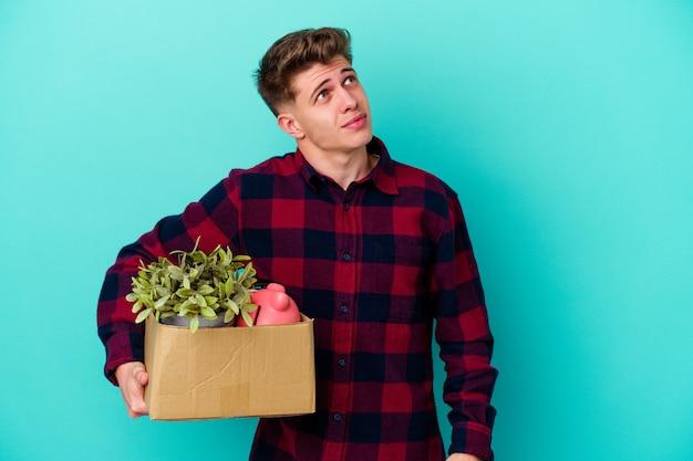 Jovem homem caucasiano se movendo segurando uma caixa isolada na parede azul, sonhando em alcançar objetivos e propósitos