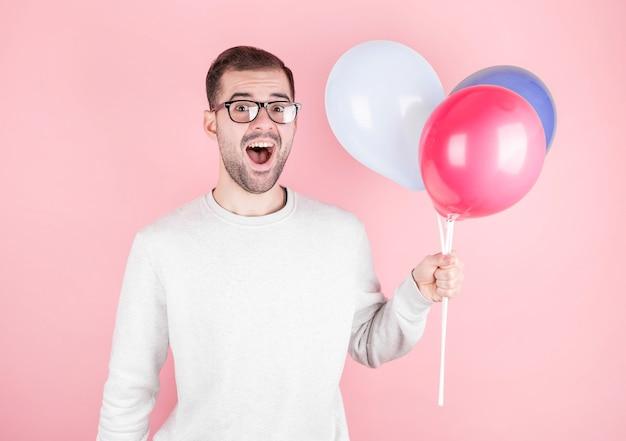 Jovem homem caucasiano segurando balões com expressão de surpresa e comemorando um aniversário de casamento isolado em uma parede rosa