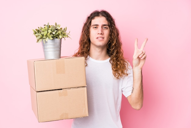 Jovem homem caucasiano segurando caixas isoladas mostrando o número dois com os dedos.