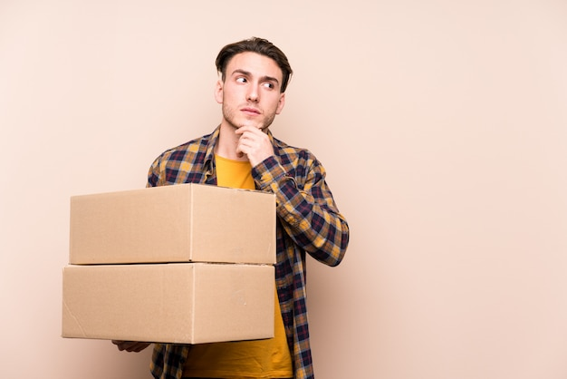 Jovem homem caucasiano segurando caixas olhando de soslaio com expressão duvidosa e cética.