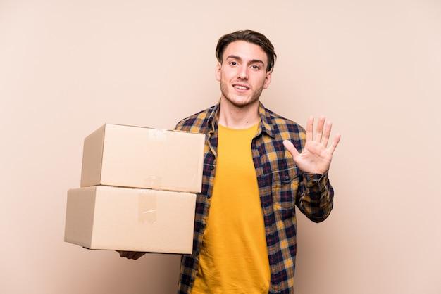 Jovem homem caucasiano segurando caixas sorrindo alegre mostrando número cinco com os dedos.
