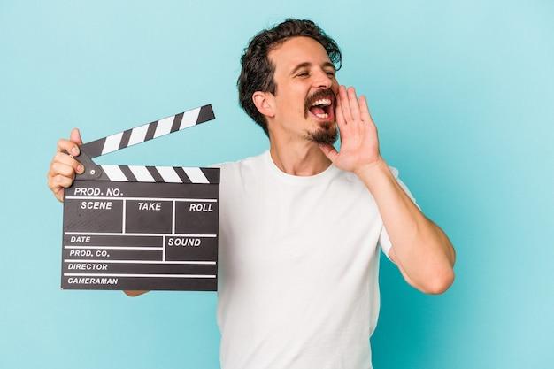 Jovem homem caucasiano segurando claquete isolada em fundo azul, gritando e segurando a palma da mão perto da boca aberta.