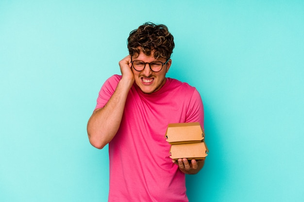 Jovem homem caucasiano segurando dois hambúrgueres isolados em um fundo azul, cobrindo as orelhas com as mãos.