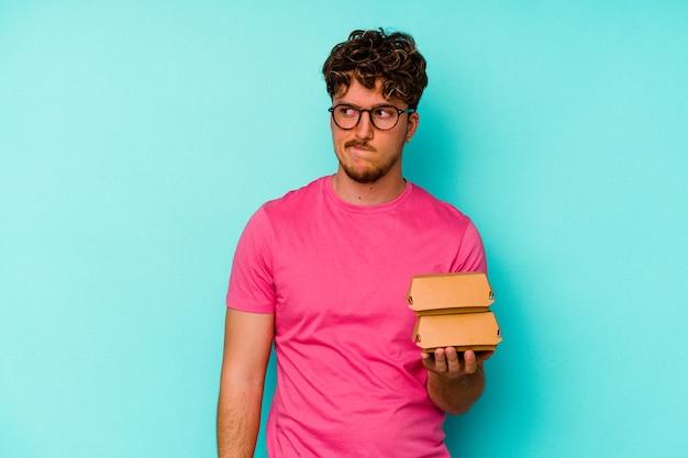 Jovem homem caucasiano segurando dois hambúrgueres isolados em um fundo azul confuso, sente-se em dúvida e inseguro.