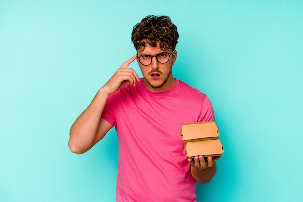 Jovem homem caucasiano segurando dois hambúrgueres isolados em um fundo azul, mostrando um gesto de decepção com o dedo indicador.