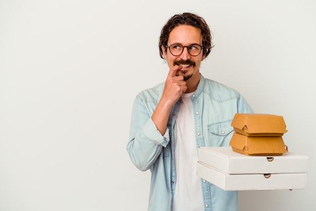 Jovem homem caucasiano segurando hambúrguer e pizzas isoladas no fundo branco relaxado pensando em algo olhando para um espaço de cópia.