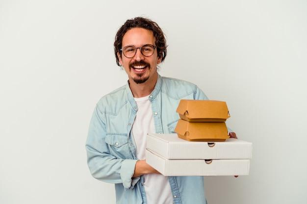 Jovem homem caucasiano segurando hambúrguer e pizzas, rindo e se divertindo.