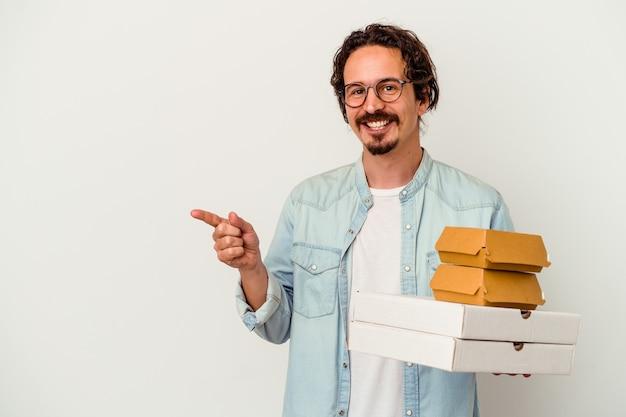 Jovem homem caucasiano segurando hambúrguer e pizzas sorrindo e apontando para o lado, mostrando algo