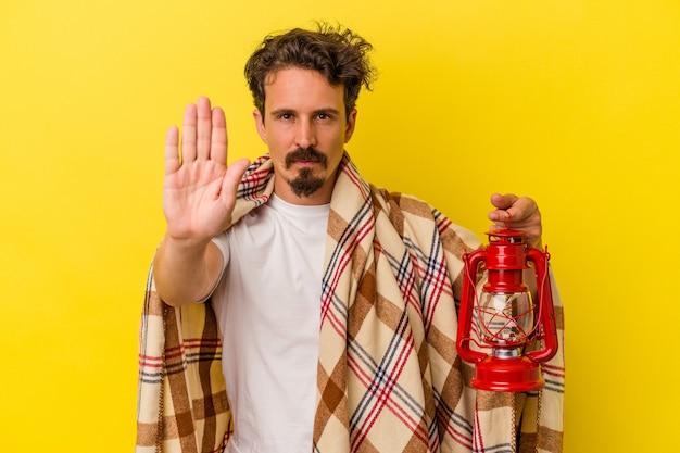 Jovem homem caucasiano segurando lanterna isolada em um fundo amarelo em pé com a mão estendida, mostrando o sinal de pare, impedindo-o.