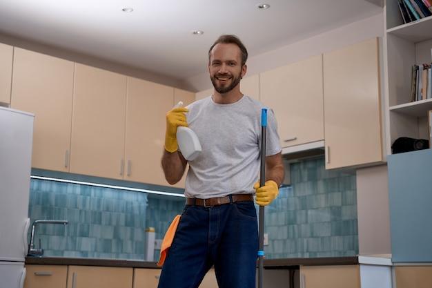 Jovem homem caucasiano segurando o esfregão e o spray de detergente