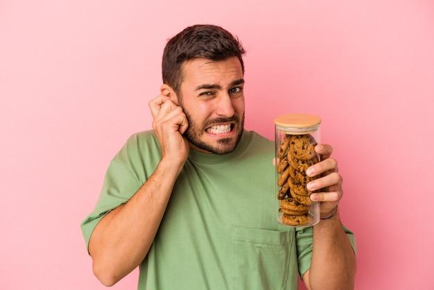Jovem homem caucasiano segurando o frasco de biscoitos isolado na parede rosa, cobrindo as orelhas com as mãos.