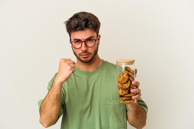 Jovem homem caucasiano segurando o frasco de biscoitos isolado no fundo branco, mostrando o punho para a câmera, expressão facial agressiva.