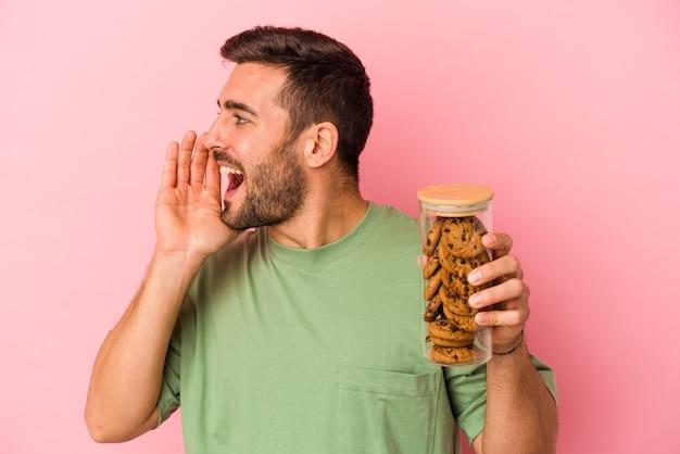 Jovem homem caucasiano segurando o frasco de biscoitos isolado no fundo rosa gritando e segurando a palma da mão perto da boca aberta.