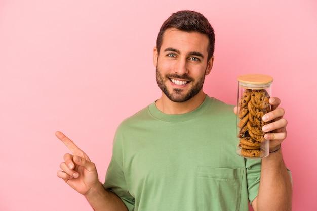 Jovem homem caucasiano segurando o frasco de biscoitos isolado no fundo rosa, sorrindo e apontando de lado, mostrando algo no espaço em branco.