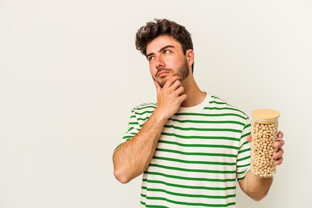 Jovem homem caucasiano segurando o frasco de grão de bico isolado no fundo branco, olhando de soslaio com expressão duvidosa e cética.