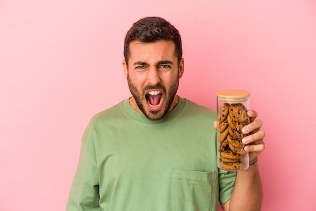 Jovem homem caucasiano segurando o pote de biscoitos isolado na parede rosa, gritando muito zangado e agressivo