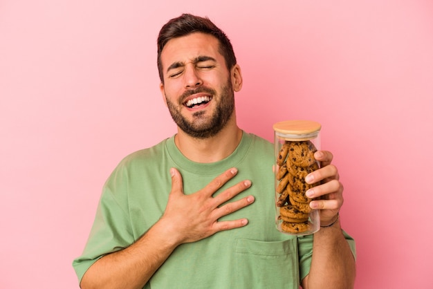 Jovem homem caucasiano segurando o pote de biscoitos isolado no fundo rosa ri alto, mantendo a mão no peito.