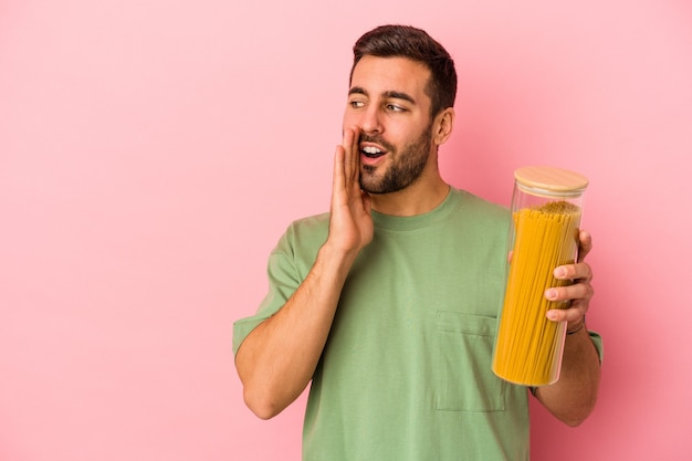 Jovem homem caucasiano segurando o pote de macarrão isolado em um fundo rosa está contando uma notícia secreta da moda e olhando de lado