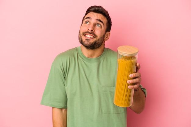 Jovem homem caucasiano segurando o pote de macarrão isolado no fundo rosa, sonhando em alcançar objetivos e propósitos