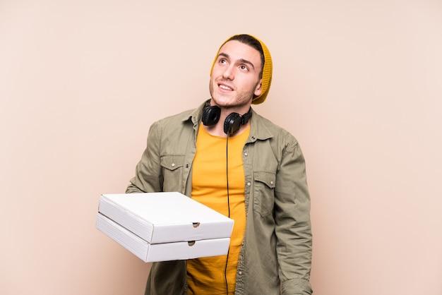Jovem homem caucasiano segurando pizza