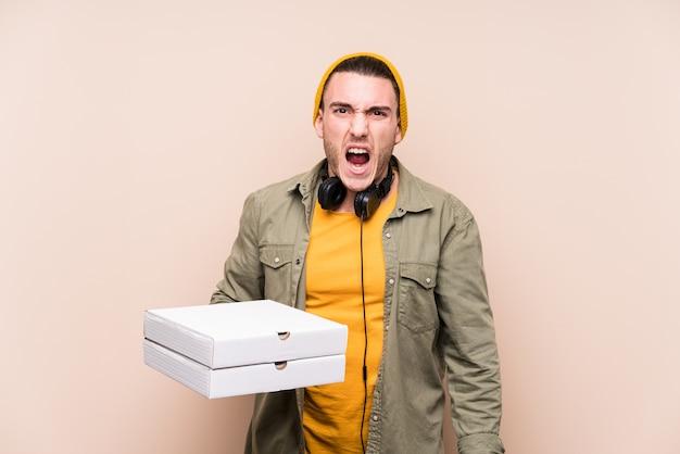 Jovem homem caucasiano segurando pizzas gritando muito irritado e agressivo.