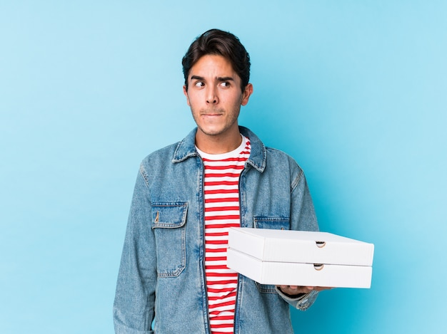 Jovem homem caucasiano segurando pizzas isoladas confusas, sente-se duvidoso e inseguro.