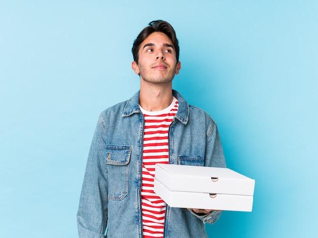 Jovem homem caucasiano segurando pizzas isoladas sonhando em alcançar metas e propósitos