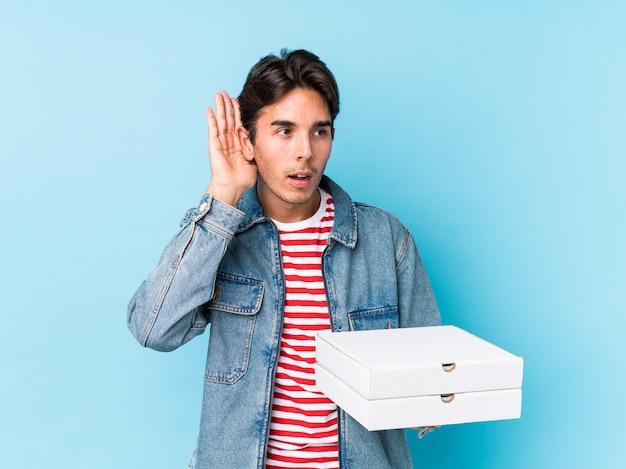 Jovem homem caucasiano segurando pizzas isoladas, tentando ouvir uma fofoca.
