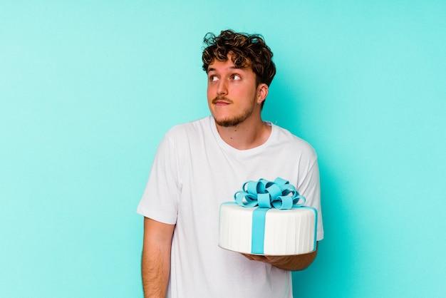 Jovem homem caucasiano segurando um bolo isolado em um fundo azul, sonhando em alcançar objetivos e propósitos