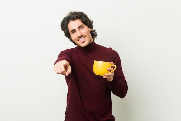 Jovem homem caucasiano segurando um café xícara alegre sorrisos apontando para a frente.