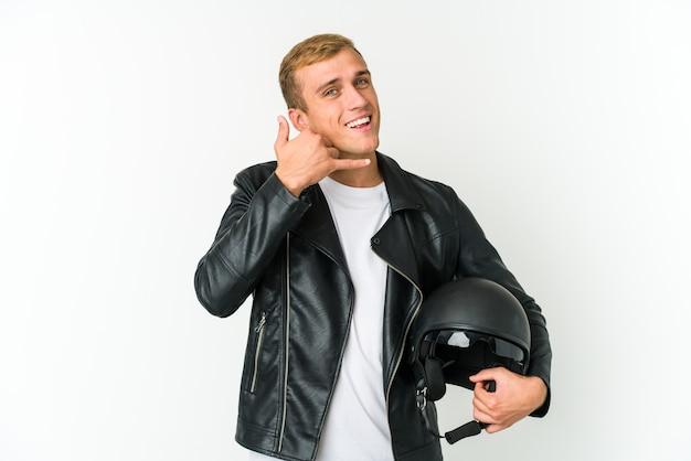 Jovem homem caucasiano segurando um capacete de moto em branco, mostrando um gesto de chamada de telefone móvel com os dedos.