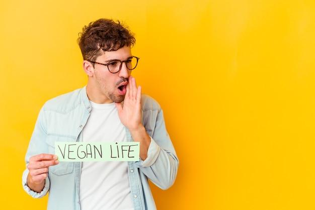 Jovem homem caucasiano segurando um cartaz da vida vegana isolado está contando uma notícia secreta de travagem e olhando para o lado