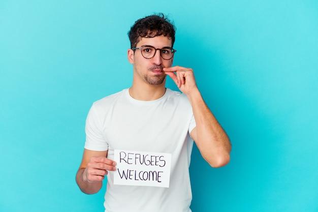 Jovem homem caucasiano segurando um cartaz de boas-vindas aos refugiados isolado com os dedos nos lábios, mantendo um segredo.