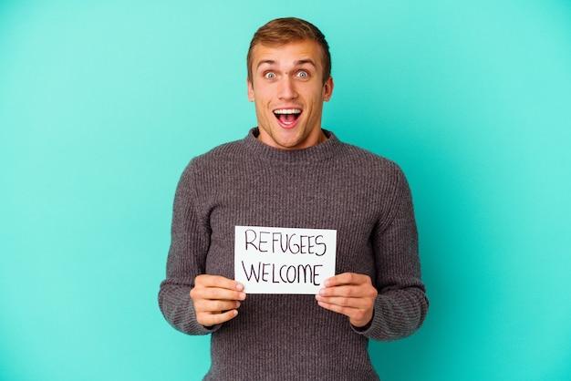 Jovem homem caucasiano segurando um cartaz de boas-vindas aos refugiados isolado sobre fundo azul