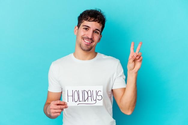 Jovem homem caucasiano segurando um cartaz de férias alegre e despreocupado, mostrando um símbolo de paz com os dedos.