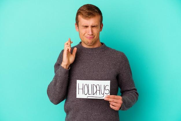 Jovem homem caucasiano segurando um cartaz de férias isolado em um fundo azul cruzando os dedos para ter sorte