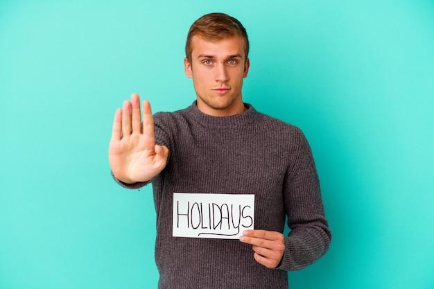 Jovem homem caucasiano segurando um cartaz de férias isolado na parede azul em pé com a mão estendida, mostrando o sinal de pare, impedindo-o.