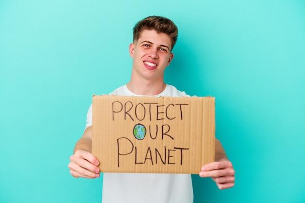 Jovem homem caucasiano segurando um cartaz de proteja nosso planeta, isolado em um fundo azul