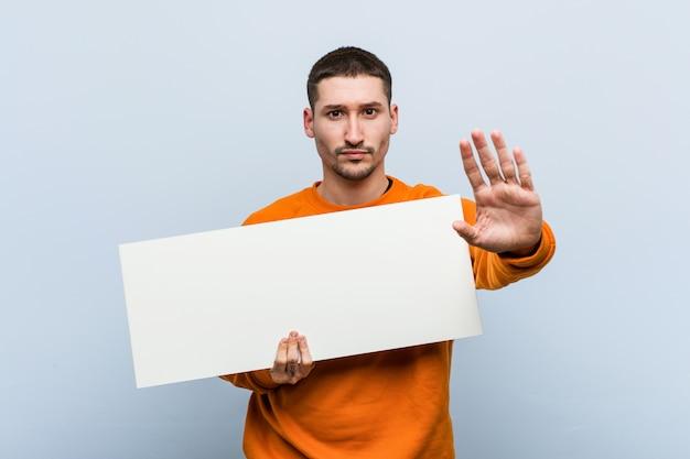 Jovem homem caucasiano segurando um cartaz em pé com a mão estendida, mostrando o sinal de stop, impedindo-o.