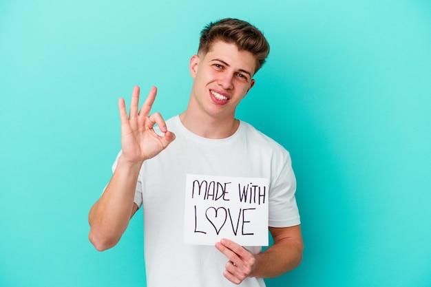 Jovem homem caucasiano segurando um cartaz feito com amor isolado na parede azul