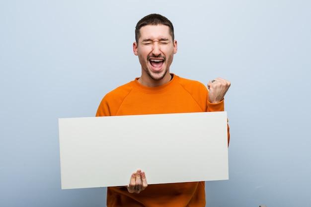 Jovem homem caucasiano segurando um cartaz torcendo despreocupado e animado. conceito de vitória