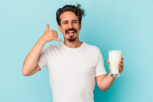 Jovem homem caucasiano segurando um copo de leite isolado em um fundo azul, mostrando um gesto de chamada de telefone móvel com os dedos.