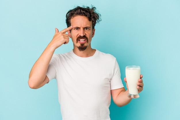 Jovem homem caucasiano segurando um copo de leite isolado em um fundo azul, mostrando um gesto de decepção com o dedo indicador.