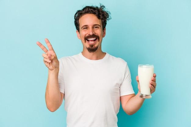 Jovem homem caucasiano segurando um copo de leite isolado no fundo azul alegre e despreocupado, mostrando um símbolo da paz com os dedos.