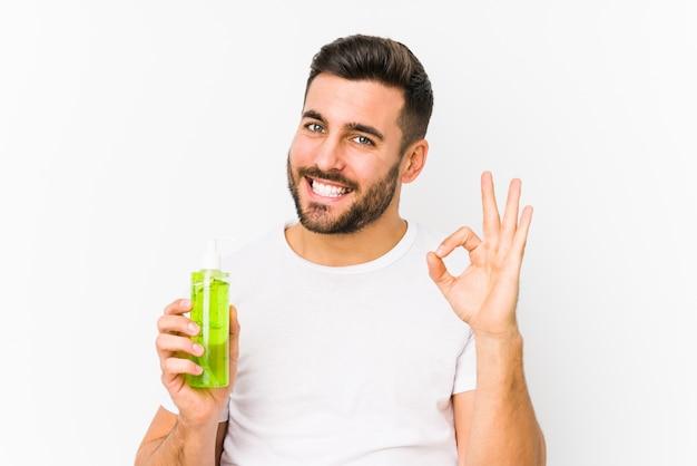 Jovem homem caucasiano segurando um creme hidratante com aloe vera alegre e confiante mostrando okey gesto.