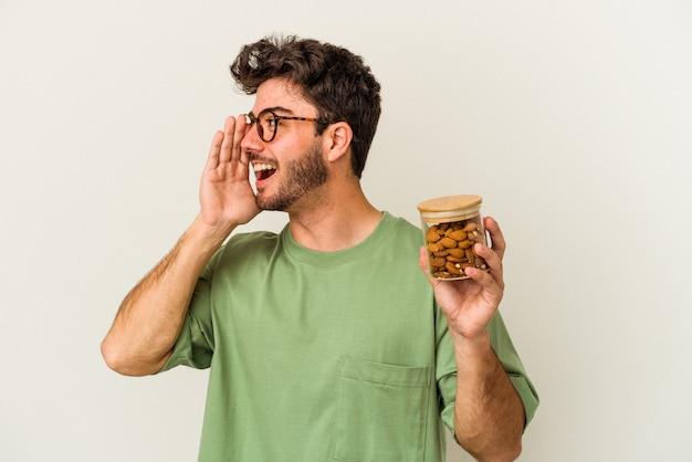 Jovem homem caucasiano segurando um frasco de amêndoa isolado no fundo branco, gritando e segurando a palma da mão perto da boca aberta.